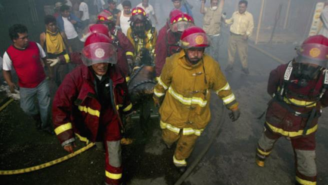 Varios bomberos llevan el cuerpo de un hombre muerto por el fuego en el incendio en Guatemala. (Daniel LeClair / REUTERS)