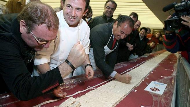 El cocinero Martín Berasategui (en el centro), junto a otros miembros de la organización, ayuda a romper la tableta de turrón (Juan Herrero / EFE).