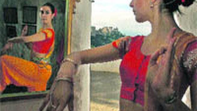 Una mujer vestida como las gitanas antiguas se mira en un espejo del museo (Torres).