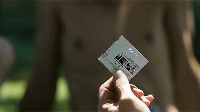 Un joven sostiene un preservativo (Archivo).