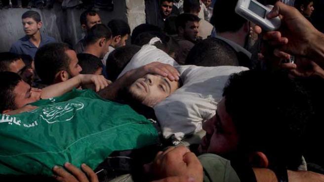 Palestinos llevan en hombros el cadáver del miliciano palestino muerto. (Ali Ali/Efe)