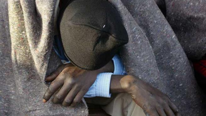 Un inmigrante descansa agotado tras llegar a Tenerife el pasado día 26 (Manuel Lérida / Efe)