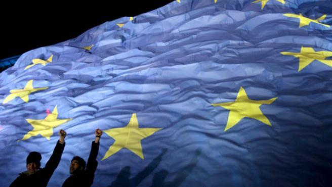 Dos personas celebran en Bucarest el ingreso de Rumanía en la UE.