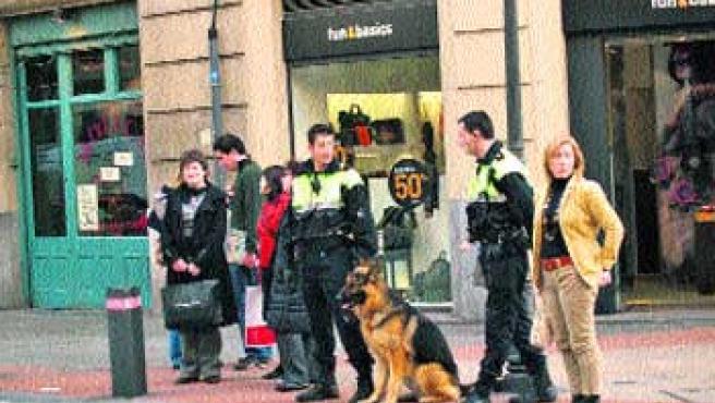 Dos agentes de la Policía Local, con el perro Drago, vigilaban ayer, la zona de Indautxu. (Begoña Hernández)