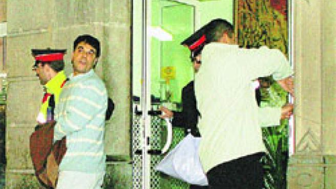 Un mosso acompaña, ayer, a uno de los arrestados. (Toni Albir / Efe)