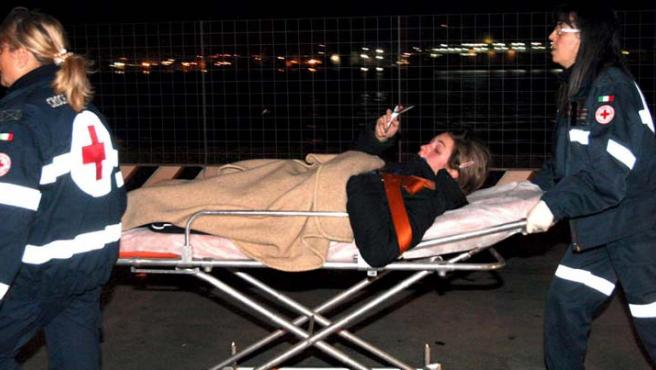 Miembros de la Cruz Roja italiana trasladan a una herida en el puerto de Mesina. (Franco Cufari / EFE)