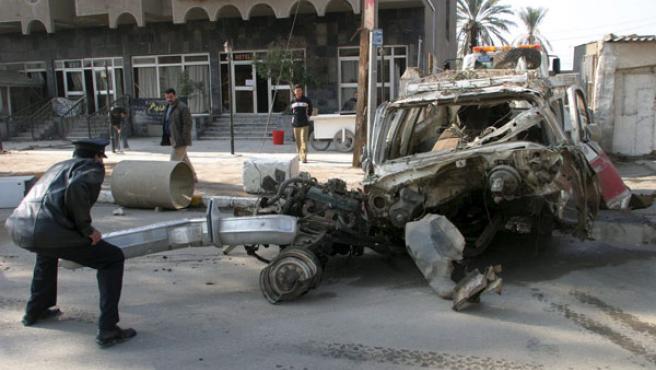 Un agente de la Policía iraquí inspecciona un vehículo destruido tras una explosión. (Mohamed Jalil / Efe)