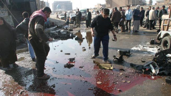 Hombres iraquíes inspecionan el lugar donde ha estallado la bomba. (Mohamed Jalil / Efe)