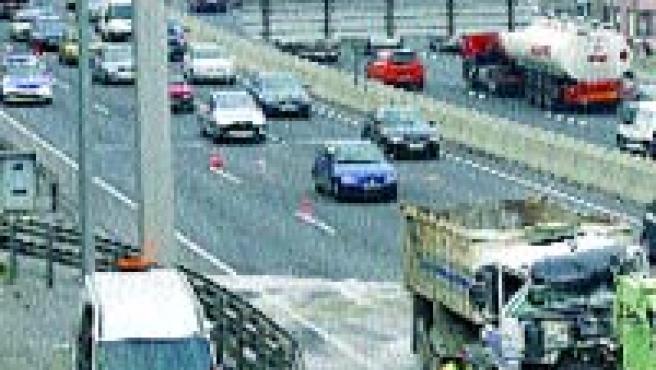 Operarios limpian la autovía, colapsada por completo.(Txema Moya/Efe)