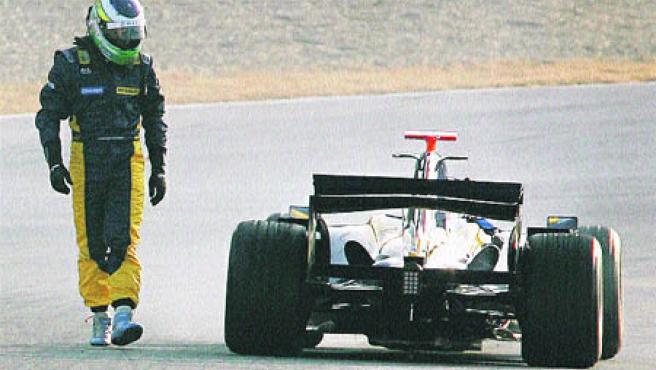 Fisichella observa su R27 parado en el circuito de Jerez. (Reuters)