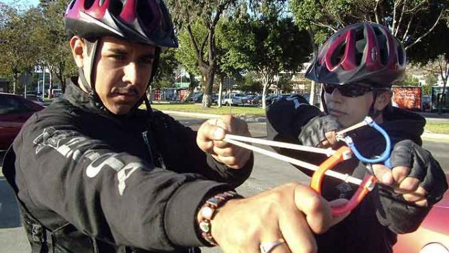 Unos policías municipales sostienen unos tirachinas mientras patrullan las calles de Tijuana. (EFE)