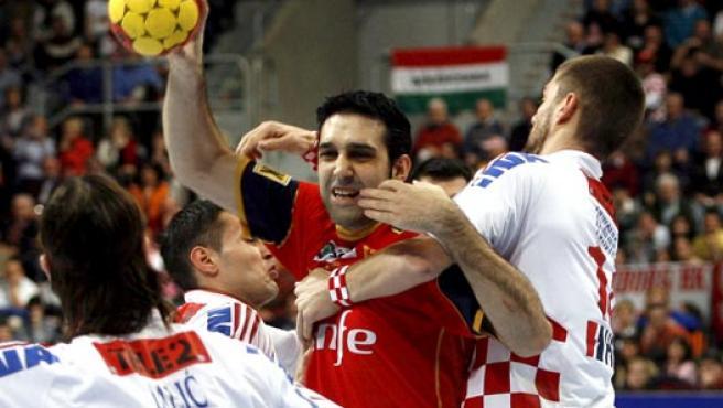 Los jugadores de Coracia Ivano Balic (izda) y Drago Vucovic (dcha) intentan bloquear el lanzamiento del jugador español Rubén Garabaya (Efe).