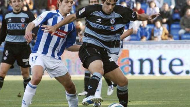 El delantero argentino de la Real Sociedad Germán Herrera (derecha) pelea un balón con el centrocampista Barber, del Recreativo de Huelva.