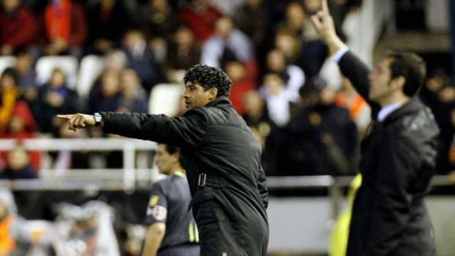 Los entrenadores del FC Barcelona, Frank Rijkaard, y del Valencia, Quique Sánchez Flores dan instrucciones a sus jugadores. (Efe)