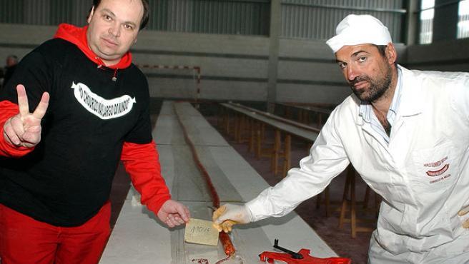 El alcalde de Melón Alberto Pardellas, y un voluntario, muestran el chorizo tradicional de 110,15 metros. (Rosa Veiga / Efe)