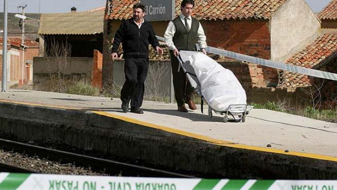 Operarios de los servicios funerarios trasladan uno de los cadáveres del matrimonio. (Brágimo / Efe)
