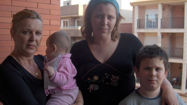 Sonia Pagán, junto a su bebé y su hijo Iván, a quien el sacerdote de Puente Tocinos exige dos años de catequesis para bautizarlo.