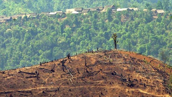 Colina desnuda de vegetación con un pueblo de agricultores de arroz y opio al fondo en Myanmar (Birmania), en la región autónoma de Wa, en el Triángulo Dorado cercada a la frontera con China, en abril de 2004.