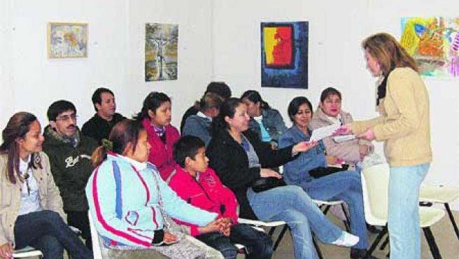 Los padres inmigrantes atienden las explicaciones del taller de la Fundación Fade. (J. L. G. G.).