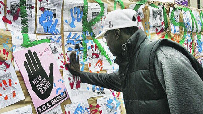 Un inmigrante, ayer, dejando su huella contra el racismo. (Toni Garriga / Efe)