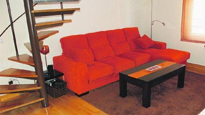 La madera, presente en el suelo y la escalera, aporta calidez al salón.