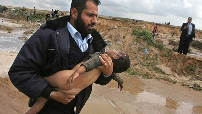 (La ampliación de esta foto puede herir la sensibilidad del lector). Un policía palestino corre con el cuerpo de un niño de 4 años. (Hatem Moussa / AP Photo)