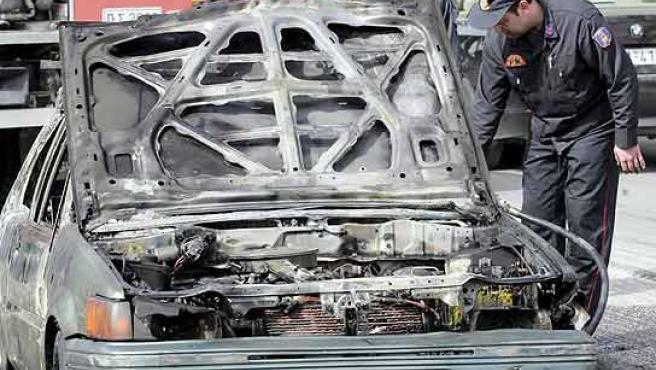 Agentes de policía griegos examinan los restos de un vehículo dañado tras los disturbios entre seguidores del Olympiakos y el Panathinaikos en marzo de 2007 (EFE).
