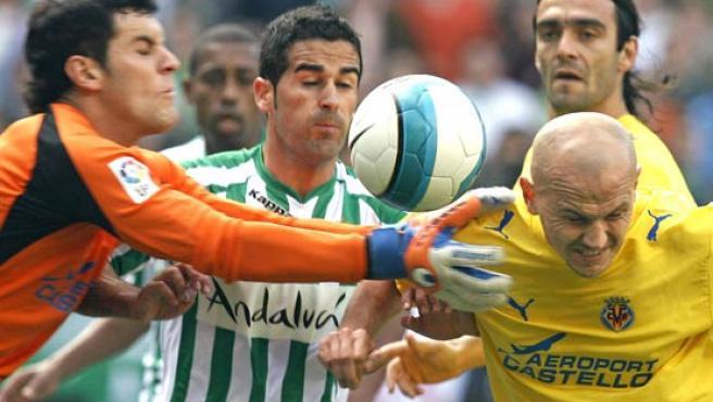 Fernando (c), lucha un balón con los jugadores del Villarreal Diego Sebastián Viera (i), y Pascal Cygan (d), en su primer partido de destierro (Efe).