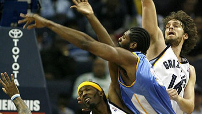 Los jugadores de los Grizzlies Pau Gasol y Hakim Warrick intentan deter al brasileño Nene, de los Nuggets.