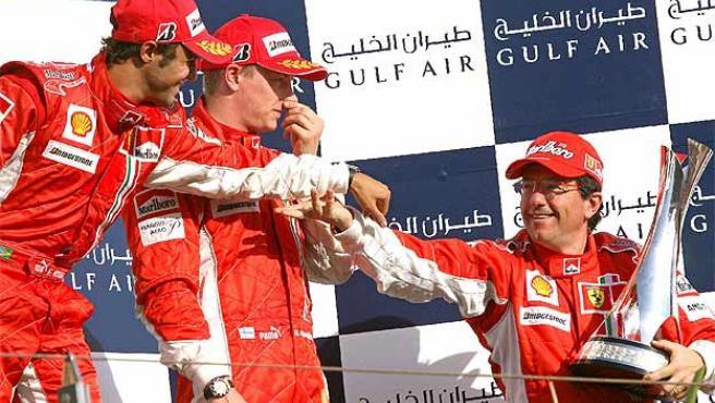 Massa (izq.), junto a Kimi Raikkonen, saluda a Luca Baldeisseri, del equipo técnico de Ferrari. (Efe)