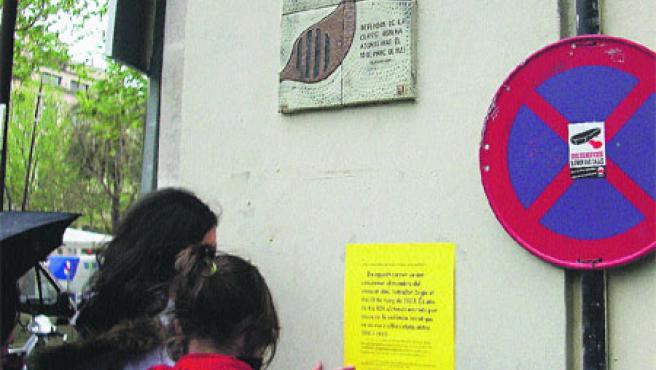 Dues alumnes pengennun cartell que recorda al Raval un sindicalista assassinat al carrer. (Ies Vil·la Romana)