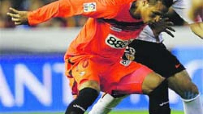 Luis Fabiano controla el balón ante el valencianista Albiol.(Manuel Bruque / EFE)