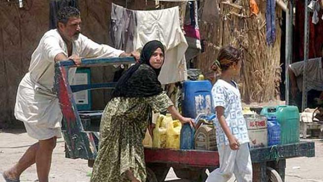 Un iraquí empuja un carro con latas llenas de agua en un campamento de refugiados para familias desplazadas en Bagdad, en junio de 2006 (Ali Abbas / EFE)