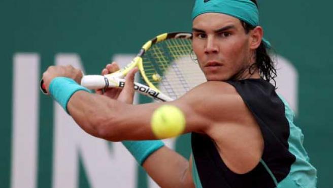 El tenista español Rafael Nadal devuelve la pelota al argentino Juan Ignacio Chela. (Efe)