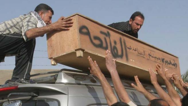 Iraquíes colocan el féretro de una de las víctimas de uno de los coched bomba de ayer (Shehab Ahmed / EFE)