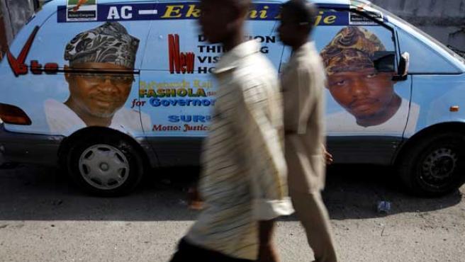 Dos hombres pasean frente a una furgoneta del partido de la oposición Congreso para la Acción en Nigeria (REUTERS/Finbarr O''Reilly)