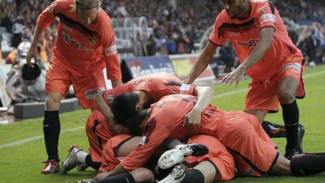 Los jugadores del Sevilla se echan encima de Jesús Navas. (Efe)