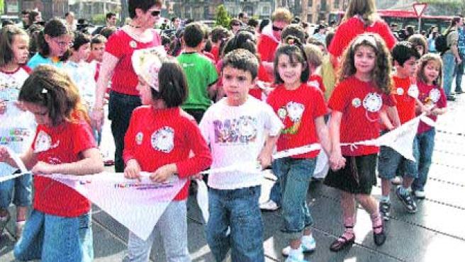 Los niños, unidos por pañuelos, portaron dorsales en los que escribieron su particular forma de reclamar educación. (Begoña Hernández)