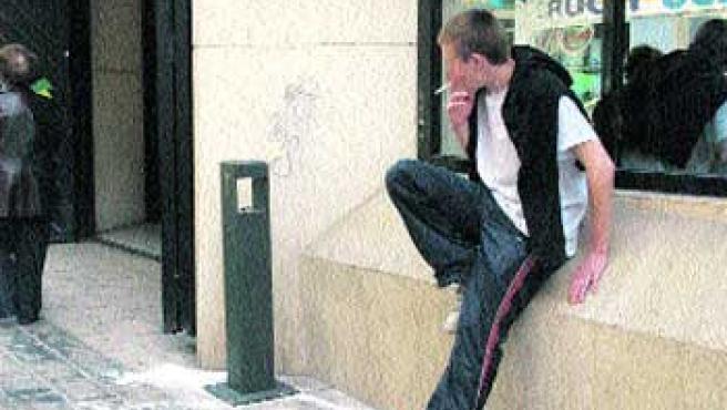 Un joven se fuma un cigarrillo junto a uno de los ceniceros instalados ayer en la calle Churruca. (Francisco González)