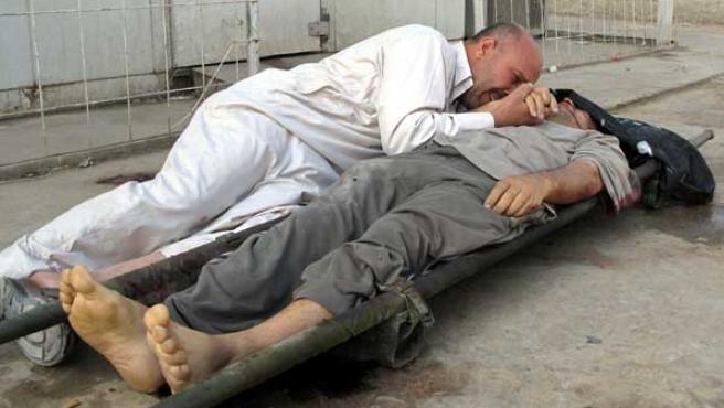 Un hombre llora sobre el cuerpo sin vida de un familiar en la morgue de Baquba (AP Photo/Adem Hadei)