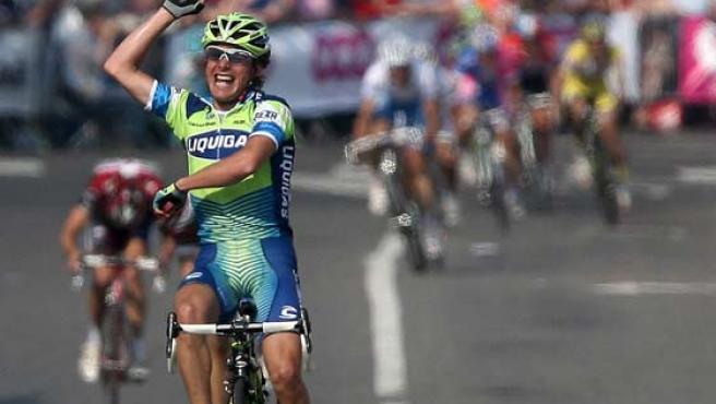 El italiano Danilo Di Luca celebra su triunfo mientras al fondo puede verse al pelotón con Valverde.