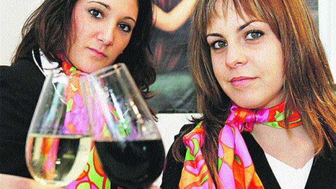 Dos azafatas de la Cata brindan con una copa de vino (R. Serrano).