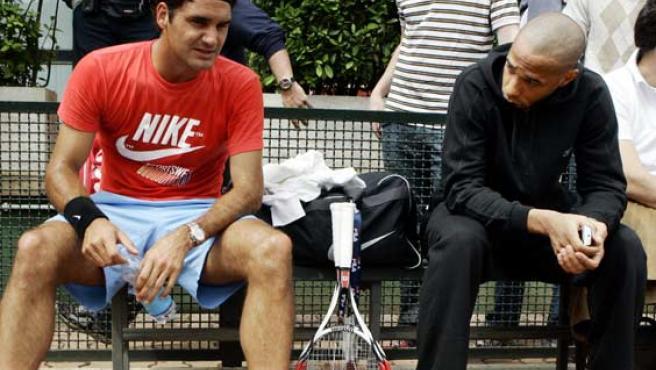 Roger Federer charla con el futbolista Thierry Henry en Roma durante un descanso de su entrenamiento.