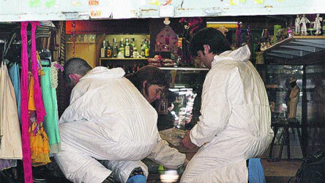 Mossos d'Esquadra analitzen proves dins la cafeteria. (A. Dalmau / Efe)
