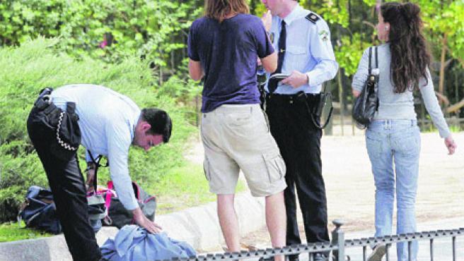 Dos agentes de la Policía Local llevan a cabo la identificación de un joven que se dedicaba a la venta ambulante en plena calle (Kako Rangel).