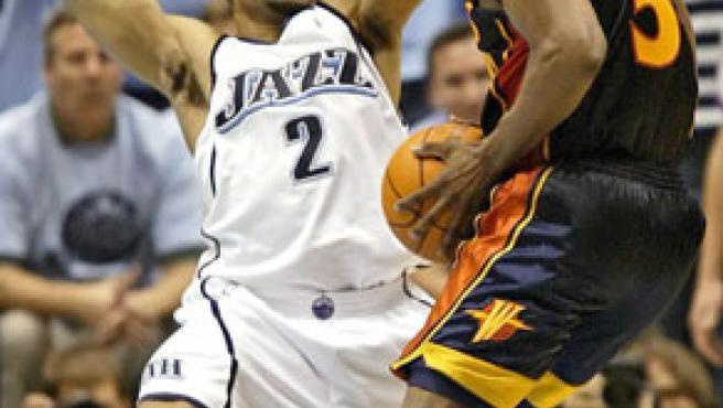 El jugador Derek Fisher (izq.), de los Jazz de Utah, lucha por el balón con Baron Davis, de los Golden State Warriors.