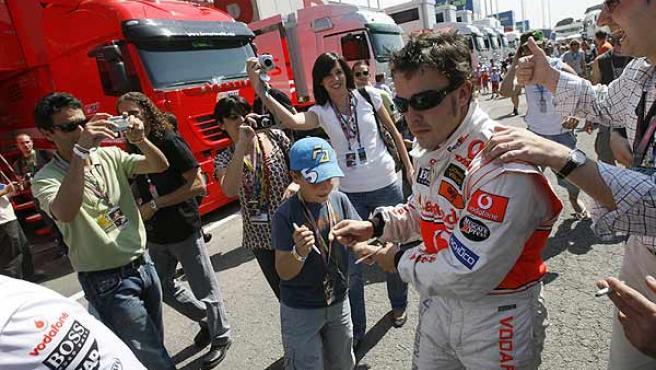 Fernando Alonso firma autógrafos en el paddock tras la segunda sesión.