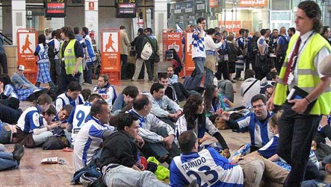 Varios aficionados del Espanyol esperan sentados en el suelo del aeropuerto de El Prat, en Barcelona. (Xavier Alsinet/ACN)
