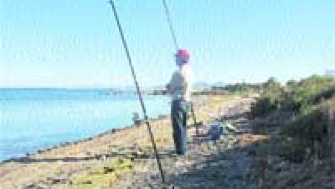 Una vecino de El Carmolí pesca en la orilla de una playa en mal estado.