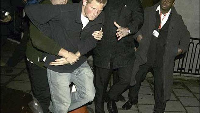 El principe Enrique de inglaterra es sujetado por personal de seguridad durante una pelea en las calles de londres eagle ©korpa